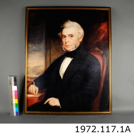 a painted portrait of a grey-haired William Hamilton Merritt. Merritt sits in an ornate red armchair and is wearing a black suit with a white shirt. Merritt holds a pen in his right hand in a gesture of writing.