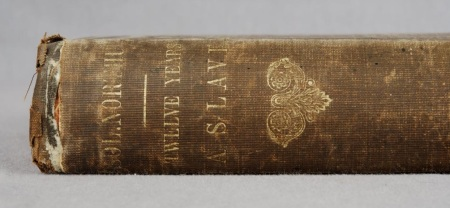 A brown book spine reads Twelve Years a Slave in gold coloured letters. The book is faded and worn.