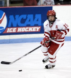 A hockey player, dressed in red and white skates across the ice holding a hockey stick with a puck in front of it. The board behind the skater reads NCAA Ice Hockey.