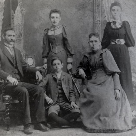 A black and white family portrait. A man, boy and woman are seated in the front row; two young girls stand in the back row. The family is dressed in fashions typical of the lat