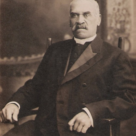 Portrait of Rev. Ball. He is seated in a chair and wearing a dark coloured suit.