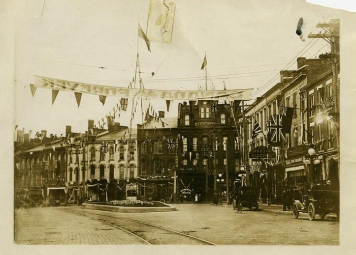 """Row of buildings in downtown St. Catharines with banner reading """"Canada Forever"""". It's believed to be for the visit of the Duke of Connaught in 1914 (St. Catharines Museum, 1975.90.2A)."""
